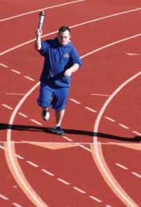 In May 2010, John Masterson carries the Olympic Torch in the Special Olympics Regional Track and Field Meet. Photo courtesy the Masterson family.