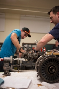Ben Bolin and John Stagg work on a turbine engine. Photo by Evan E. Duran.